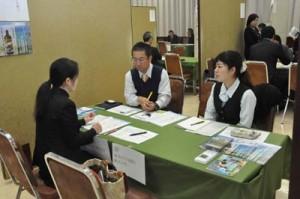 合同面接会会場で求職者に事業内容を説明する企業担当ら=29日、奄美市名瀬