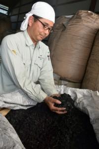 炭作りに取り組む田中さん。炭は用途に合わせて5、10、20㍉などの大きさにして販売している=奄美市笠利町