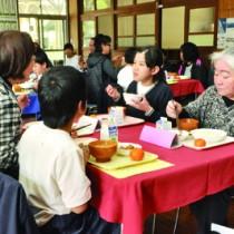 地域住民と一緒に食事を味わう児童ら=24日、住用小学校