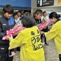 歓迎の花束を受け取る(右から)三浦監督と赤尾公選手=18日、奄美市笠利町の奄美空港