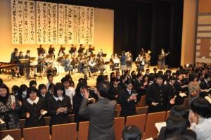 フィナーレで参加校選抜メンバーの演奏に合わせて合唱する高校生ら。ステージに掲げられているのは歌詞で、各校書道部が書いた=19日、あしびの郷・ちな