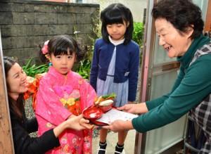 親戚宅でナンカンジョセを受け取る大重杏奈ちゃん=7日、龍郷町