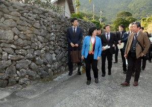 阿伝集落のサンゴの石垣を視察する奄美群島振興開発審議会の委員ら=31日、喜界町