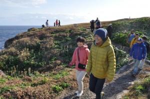 沖永良部島で設定予定のトレイルコースを歩く交流会参加者=17日、知名町の田皆岬