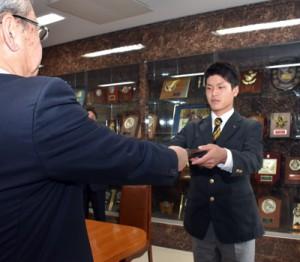 優秀選手の表彰を受けて記念の盾を受け取る前川君=24日、鹿児島市の鶴丸高校