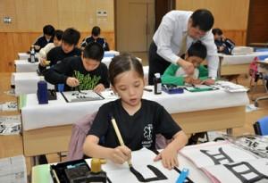 集中して筆を運ぶ児童生徒=6日、大和村防災センター