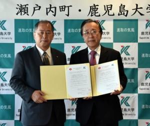 協定書を手にする鎌田町長(左)と熊本病院長=15日、鹿児島市の鹿児島大学病院