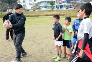 パスの動作を指導する重一生(左)=18日、奄美市の長浜緑地公園