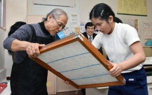 安田さんの指導を受け、卒業証書を手作りする川畑さん(右)=23日、名音小学校