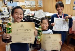 日本バッハコンクールに出場した(左から)尾前駿海君、北原日菜子さん。日本ピアノコンクールinかごしま本選に出場する尾前怜珠さん(右)=17日、奄美市名瀬