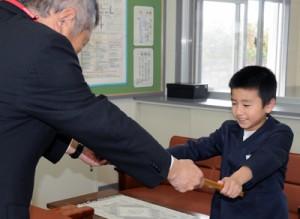 優秀賞に選ばれ、賞状を受け取る平島颯大君=2日、奄美市の屋仁小学校