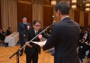 黒糖焼酎部門を代表して三反園知事から表彰状を受け取る西平本家の小畠社長=10日、鹿児島市のホテル
