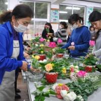 徳之島産のトルコギキョウを使ったフラワーアレンジメントに挑戦した参加者ら=23日、井之川中学校