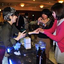 黒糖焼酎の試飲を楽しむ「奄美黒糖焼酎と農林水産物を楽しむ会」の参加者ら=24日、奄美市名瀬