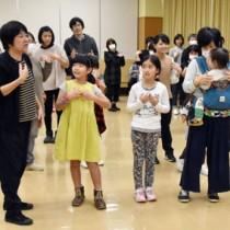 方言のわらべ歌を口ずさみながら遊ぶ参加者=19日、県立奄美図書館