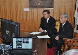 光ブロードバンドの開通を記念し、テレビ会議システムで対談する朝山毅市長(右)ら=1日、奄美市役所