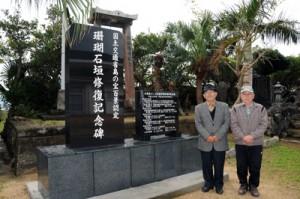 建立した「珊瑚石垣修復記念碑」前に立つ与路珊瑚石垣保護組合の(左から)福島組合長、福山副組合長=13日、与路島