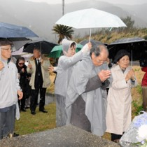 犠牲者を仮埋葬した海岸に手を合わせる対馬丸遺族団=18日、大和村