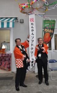 くす玉を割って販売開始をアピールする伊集院村長(左)ら=14日、大和村