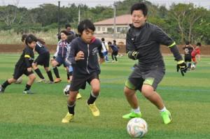 完成した人工芝グラウンドでサッカー元日本代表の海堀さん(右)と競り合う小学生ら=25日、与論町