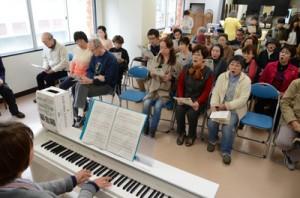震災犠牲者や被災者に祈りを込めて歌う参加者=11日午後2時50分すぎ、奄美市名瀬のビル