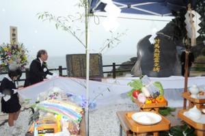慰霊碑を除幕する遺族や地元の小中学生=19日、宇検村・船越海岸