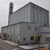 完成した与論町の新ごみ焼却処理施設(上)と施設2階の中央制御室から見たごみピット=28日、同町立長