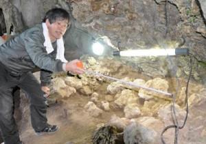 下原洞穴遺跡で発見された石棺墓を調査する竹中教授(上)と、石鏃を製作する道具や石材=30日、天城町