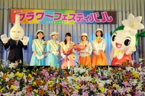 新おきのえらぶ島観光大使に決まった増本さん(中央)を囲んで記念撮影=12日、和泊中体育館