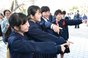 受験番号を確認し、友人と喜び合う受験生=15日、奄美市名瀬の県立大島高校