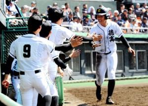 先制のホームを踏んでベンチに迎えられる徳之島の澤村=4日、鴨池野球場