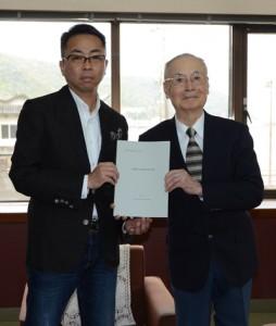 勝座長から計画書を受け取った山田会長(右)=3月31日、奄美市名瀬の紬会館