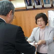 朝山市長に報告書を手渡す向井委員長(右)=20日、奄美市役所