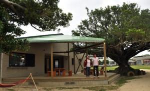 喜界島サンゴ礁科学研究所の敷地内に新設された研究・展示棟(上)と、完成祝賀会=7日、喜界町早町