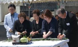 祭壇に献花して犠牲者のみ霊を慰める遺族ら=21日、徳之島町