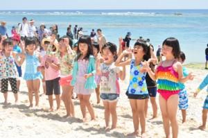海開きイベントで、海をバックに浜辺でダンスを踊る園児ら=23日、知名町屋子母海岸