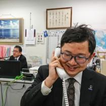 電話応対にも意気込みがあふれている隈元さん=11日、奄美市東京事務所