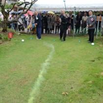始球式でパークゴルフ場の完成を祝う関係者=13日、奄美市名瀬有良