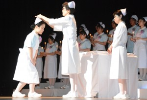 看護学科2年の学生にナースキャップが授けられた奄美看護福祉専門学校の戴帽式=12日、奄美文化センター