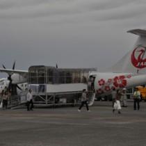 奄美空港に就航したJACの新型機と搭乗客ら=28日、奄美市笠利町