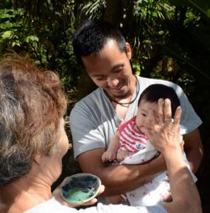 赤ちゃんの額にすすを付け、健やかな成長を祈るナブェヒグル=30日、奄美市笠利町