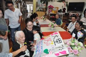 105歳の誕生日を迎えた、沖永良部島最高齢の大里秋さん(左手前)=25日、和泊町国頭