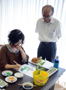日本画の描き方を指導する西村さん(右)=14日、奄美パーク