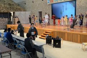 2団体が輪踊りを繰り広げた舞台終盤と来場者へ茶を振る舞うわれもこう会員=4日、奄美市笠利町