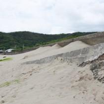 護岸を覆う勢いの浜砂=24日、龍郷町秋名集落の海岸