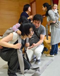熊本県天草地方発祥のおんぶひも「もっこ」を体験する参加者=4日、奄美市名瀬