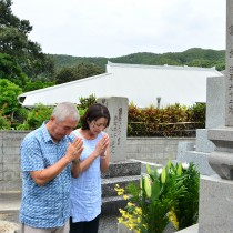 亡父の古里で墓前に手を合わせるフランクさん(左)と妻ダイアンさん=20日、瀬戸内町蘇刈