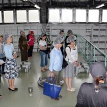 焼酎の蒸留工程について学ぶ参加者ら=20日、龍郷町大勝の町田酒造
