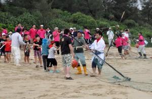 二手に分かれ網を引っ張る参加者ら=7日、徳之島町花徳