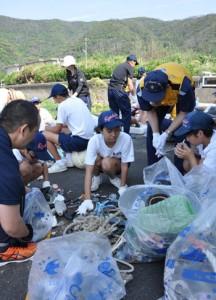 奄美海保の職員と漂着ごみ調査で集めたごみを分類する生徒たち=10日、龍郷町の嘉渡海岸